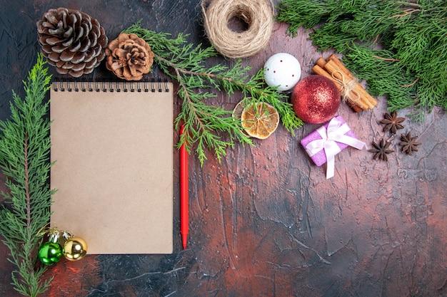 상위 뷰 빨간 펜 노트북 소나무 나뭇 가지 크리스마스 트리 볼 장난감 및 선물 계피 아니스 짚 스레드 진한 빨간색 표면 무료 장소 무료 사진