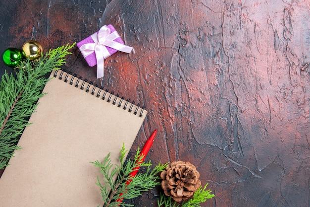 상위 뷰 빨간 펜 노트북 소나무 나뭇 가지 크리스마스 트리 볼 장난감 및 여유 공간이있는 어두운 빨간색 표면에 선물 무료 사진