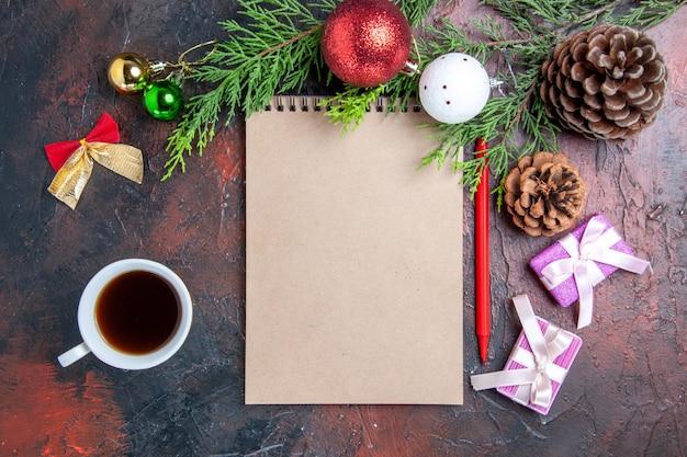 상위 뷰 빨간 펜 노트북 소나무 나무 가지 크리스마스 트리 볼 장난감 및 선물 어두운 빨간색 표면에 차 한 잔 무료 사진
