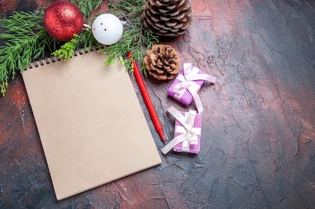 上面図赤ペンノートブック松の木の枝クリスマスツリーボールのおもちゃと濃い赤の表面の空きスペースの贈り物 無料写真