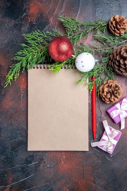 上面図赤ペンノートブック松の木の枝クリスマスツリーボールのおもちゃと濃い赤の表面の贈り物 無料写真