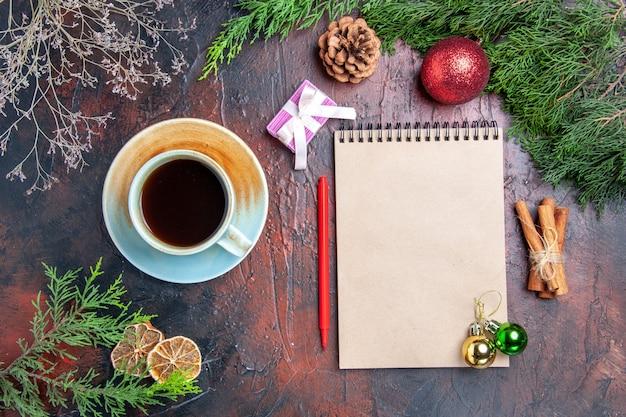 上面図赤ペンノートブック松の木の枝クリスマスツリーボールおもちゃシナモンは濃い赤の表面にお茶を貼り付けますクリスマス写真 無料写真