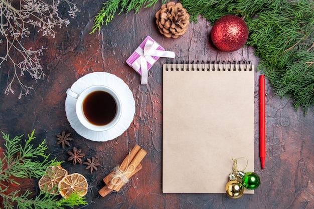 上面図赤ペンノートブック松の木の枝クリスマスツリーボールおもちゃシナモンは濃い赤の表面にお茶の星のアニスのカップを貼り付けますクリスマス写真 無料写真