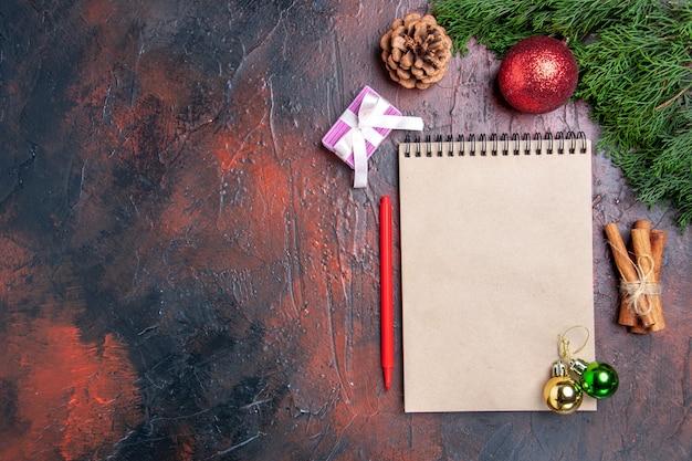 上面図赤ペンノートブック松の木の枝クリスマスツリーボールおもちゃシナモンスティック濃い赤の表面の空きスペースクリスマス写真 無料写真