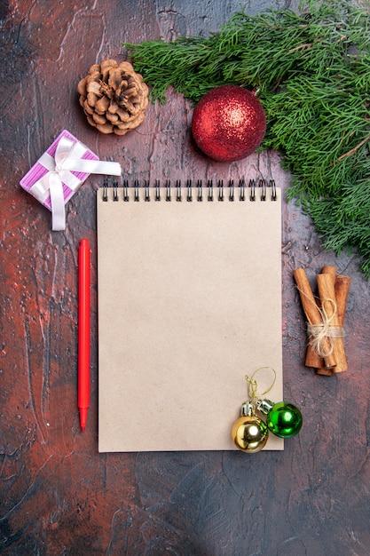 상위 뷰 빨간 펜 노트북 소나무 나뭇 가지 크리스마스 트리 볼 장난감 계피는 어두운 빨간색 표면 크리스마스에 스틱 Photo 무료 사진