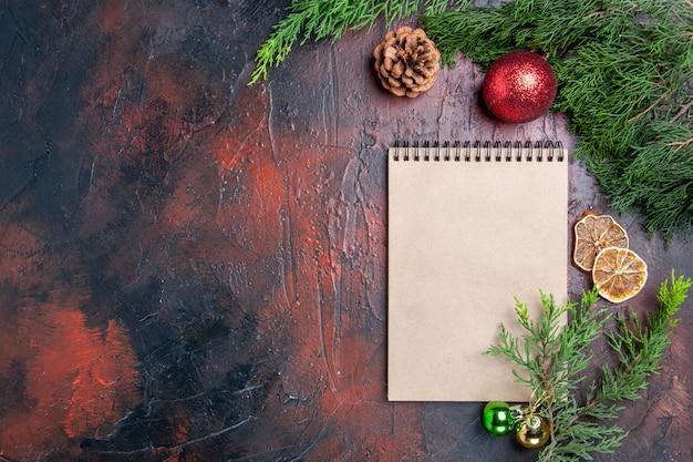 상위 뷰 빨간 펜 노트북 소나무 나무 가지 크리스마스 트리 볼 장난감 말린 레몬 슬라이스 어두운 빨간색 표면 여유 공간 크리스마스에 차 한잔 사진 무료 사진