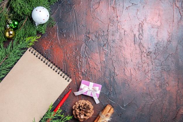 上面図赤ペンノートブック松の木の枝クリスマスツリーボールおもちゃ濃い赤の表面の空きスペース 無料写真