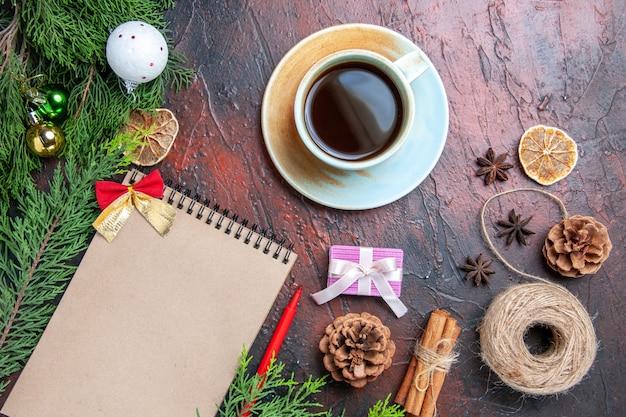 上面図赤ペンノートブック松の木の枝クリスマスツリーボールおもちゃわら糸スターアニス暗赤色の表面のお茶のカップコピースペース 無料写真