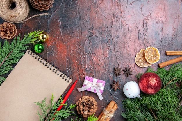 상위 뷰 빨간 펜 노트북 소나무 나무 가지 크리스마스 트리 공 및 선물 계피 아니스 짚 실 말린 레몬 조각 어두운 빨간색 표면 여유 공간에 무료 사진