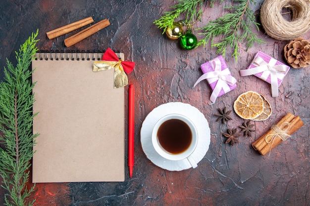 Вид сверху красная ручка тетрадь сосновые ветки елочные игрушки и подарки чашка чая белое блюдце корица с анисом на темно-красной поверхности Бесплатные Фотографии