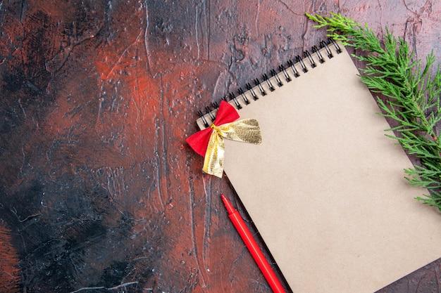 Вид сверху красная ручка блокнот с бантиком ветка сосны справа от темно-красной поверхности с местом для копирования Бесплатные Фотографии