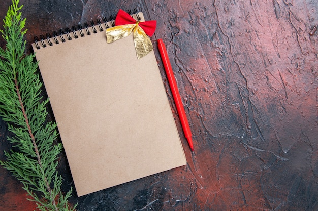 Вид сверху красная ручка блокнот с маленьким бантом ветка сосны на темно-красной поверхности копией пространства Бесплатные Фотографии