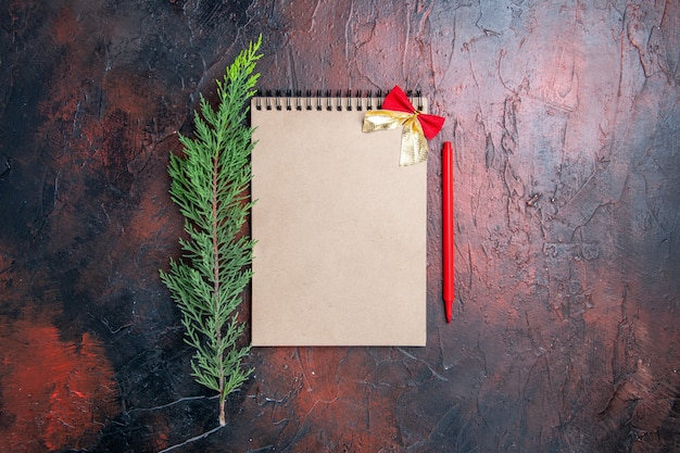 Вид сверху красная ручка на блокноте с маленьким бантом ветка сосны на темно-красной поверхности с копией пространства Бесплатные Фотографии