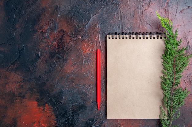 Вид сверху красная ручка блокнот с бантом ветка сосны на темно-красной поверхности с местом для копирования Бесплатные Фотографии