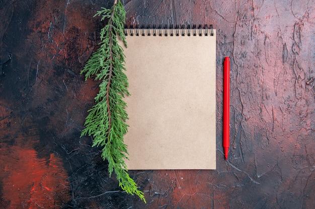 Вид сверху красная ручка блокнот с бантиком ветка сосны на темно-красной поверхности с копией пространства Бесплатные Фотографии