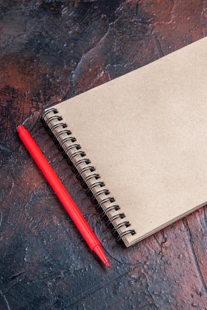 Вид сверху красная ручка блокнот с бантом на темно-красной поверхности Бесплатные Фотографии