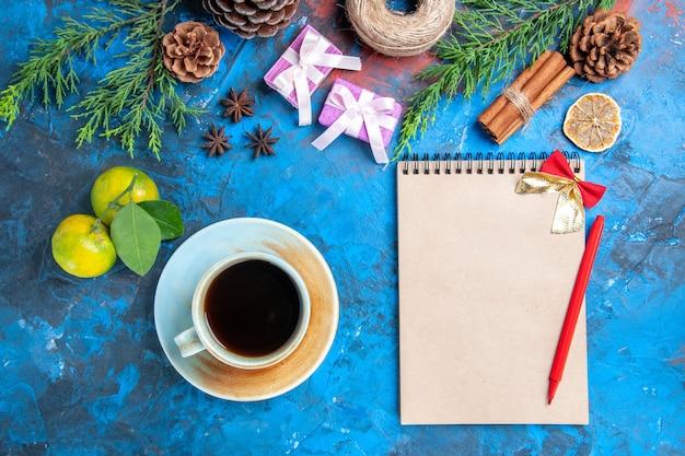 Вид сверху красная ручка лук тетрадь ветки сосны шишки палочки корицы чашка чая анисов соломенная нить мандарины на синей поверхности Бесплатные Фотографии
