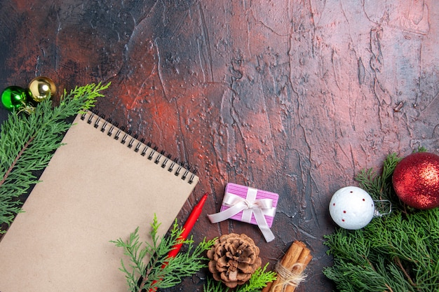 Vista dall'alto penna rossa un taccuino albero di pino rami albero di natale giocattoli e regalo cannella anice filo di paglia sul tavolo rosso scuro posto libero Foto Gratuite