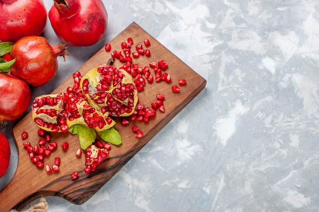 Top view red pomegranate fresh and juicy fruits on the white desk Free Photo