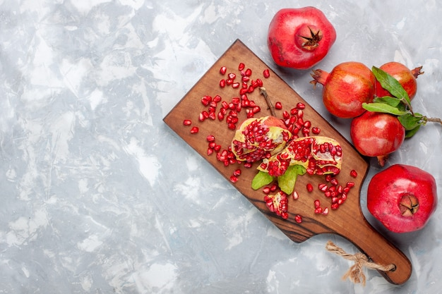 Top view red pomegranate fresh and juicy fruits on white desk Free Photo