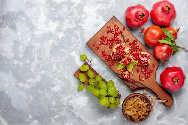 Frutta fresca e succosa del melograno rosso di vista superiore con l'uva sullo scrittorio bianco Foto Gratuite