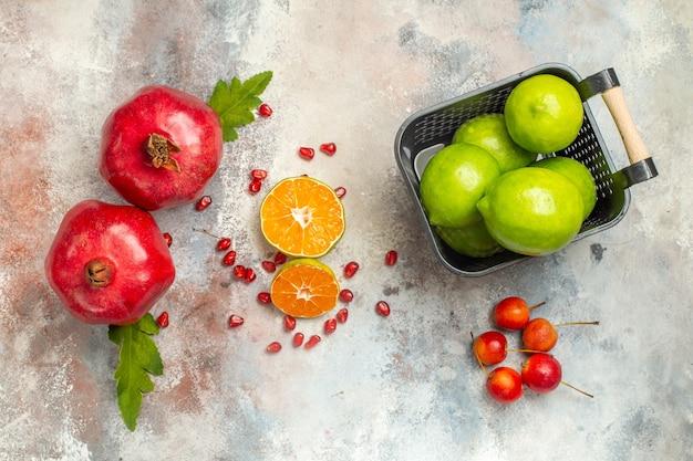 Вид сверху красные гранаты, дольки лимона, лимоны в миске небесные яблоки на обнаженной поверхности Бесплатные Фотографии