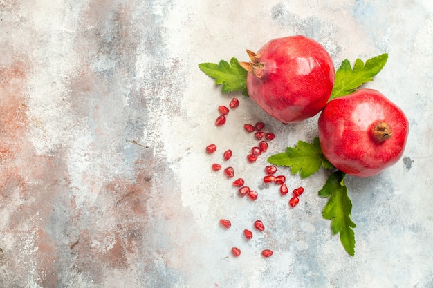 Top view red pomegranates pomegranate seeds on nude surface with copy space Free Photo