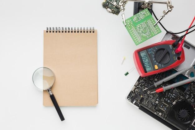 Вид сверху на ремонт ноутбука с помощью блокнота Бесплатные Фотографии