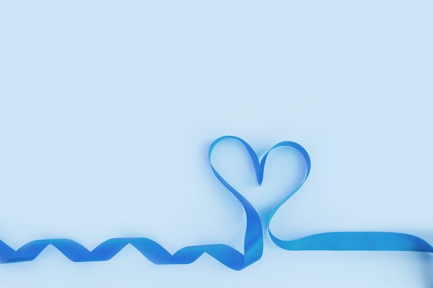 Top view of ribbon shaped as heart on blue background. valentine's day concept Premium Photo