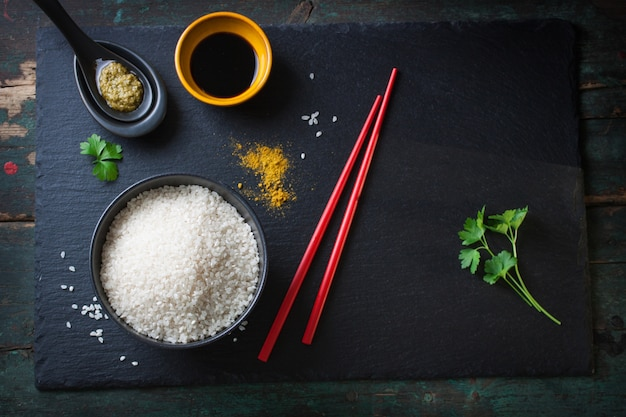 Top view of rice bowl next to red chopsticks Free Photo