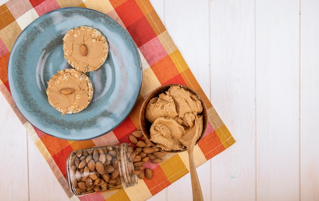 Top view of rice cereal cracker with peanut paste butter on blue ceramic plate almond scattered from a glass jar and a bowl with peanut butter on plaid table napkin on white wooden background wi Free Photo