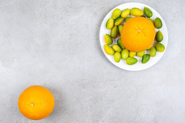 Top view of ripe orange with pile of kumquats on white plate. Free Photo