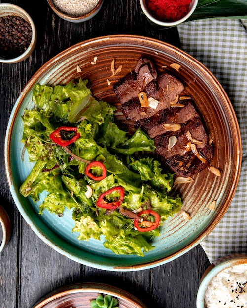 Top view of roasted beef with lettuce and red chili pepper on a plate on wood Free Photo