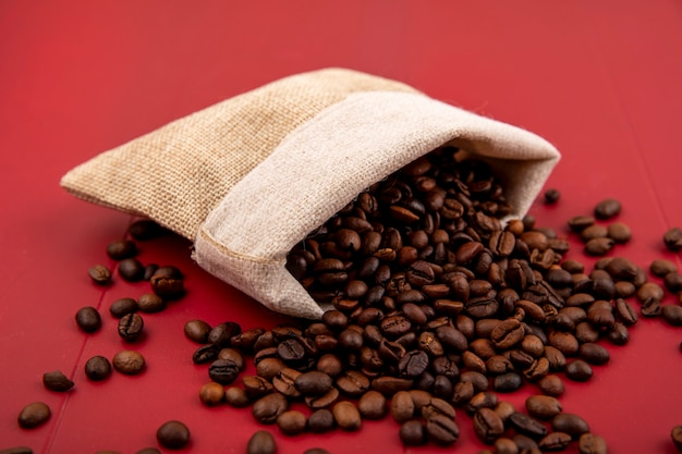 Top view of roasted coffee beans falling out of a burlap bag on a red background Free Photo