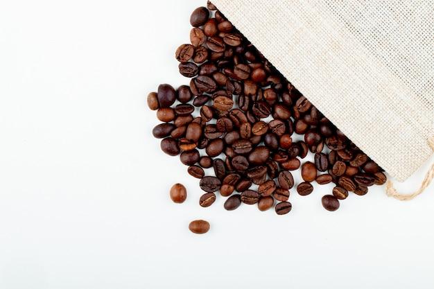 La vista superiore dei chicchi di caffè arrostiti ha sparso da un sacco su fondo bianco con lo spazio della copia Foto Gratuite