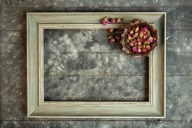 Top view rose tea in bowl and a wooden empty frame Free Photo