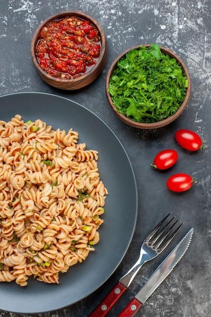 Вид сверху ротини макароны на серой тарелке томатный соус нарезанная петрушка в небольших мисках помидоры черри вилка и нож на темном столе Бесплатные Фотографии
