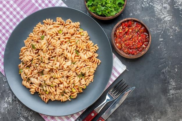회색 테이블에 그릇에 분홍색 흰색 체크 무늬 냅킨 포크와 나이프 다진 채소와 토마토 소스에 접시에 상위 뷰 Rotini 파스타 무료 사진