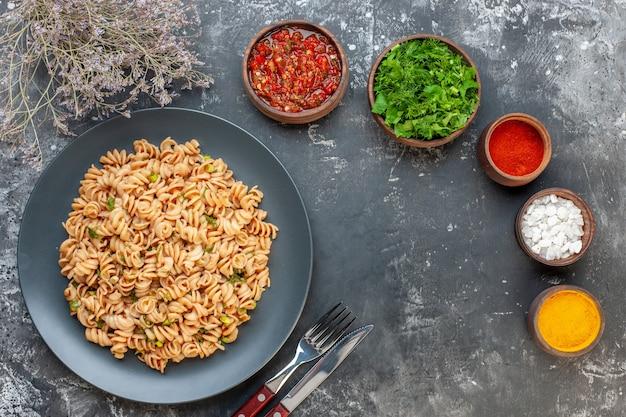 Pasta rotini vista dall'alto su piatto rotondo forchetta e coltello sale marino curcuma pepe rosso in polvere in piccole ciotole sul tavolo grigio Foto Gratuite