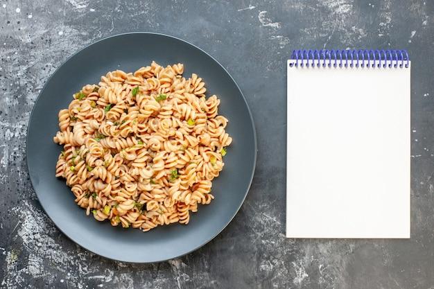 Top view rotini pasta on round plate notepad on dark surface Free Photo