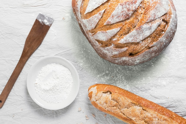 Top view round bread and french baguette with flour Free Photo