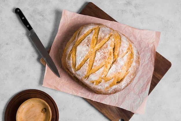Top view round bread with knife on baking paper Free Photo