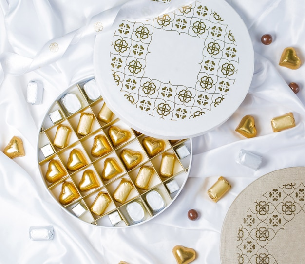 Top view of round chocolate box with golden and silver wrapped chocolates Free Photo