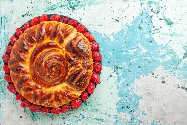 Vista dall'alto rotonda deliziosa torta con fragole rosse fresche sulla scrivania blu Foto Gratuite
