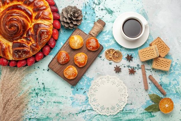 Vista dall'alto rotonda deliziosa torta con torte di fragole rosse fresche e tazza di tè sulla superficie blu Foto Gratuite