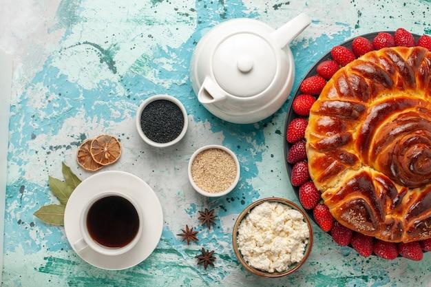 Вид сверху круглый вкусный пирог со свежей клубникой на голубой поверхности Бесплатные Фотографии