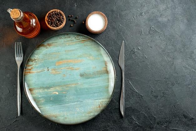 Vista dall'alto piatto rotondo cena coltello e forchetta pepe nero e olio di sale bottiglia sulla tavola nera con spazio libero Foto Gratuite