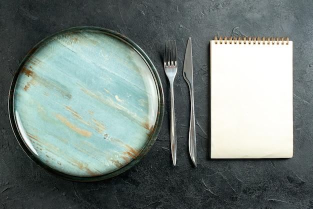 상위 뷰 라운드 플래터 강철 포크와 블랙 테이블에 저녁 식사 칼 노트북 무료 사진