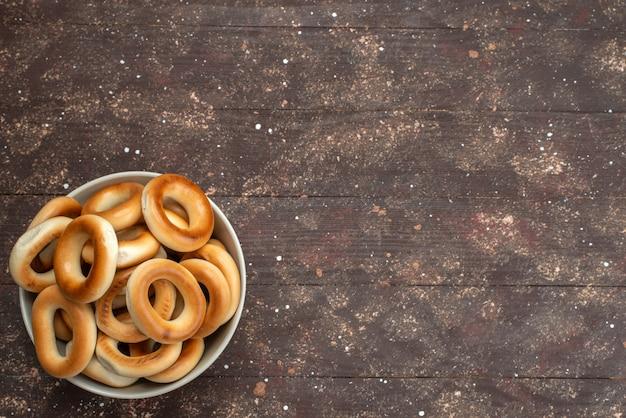 Вид сверху круглые вкусные крекеры сладкие и сушеные внутри пластины на коричневый, сухарики чипсы бисквитный сладкий Бесплатные Фотографии