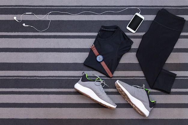 Top view of running shoes, womens clothes, pants tights, smartphone run application on gre Premium Photo